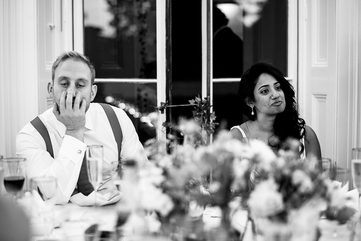 bride and incredibly bored looking groom sit and listen to wedding speech