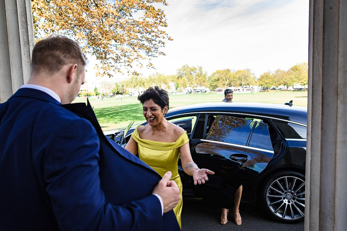 wedding guest compliments groom's suit as she arrives in car