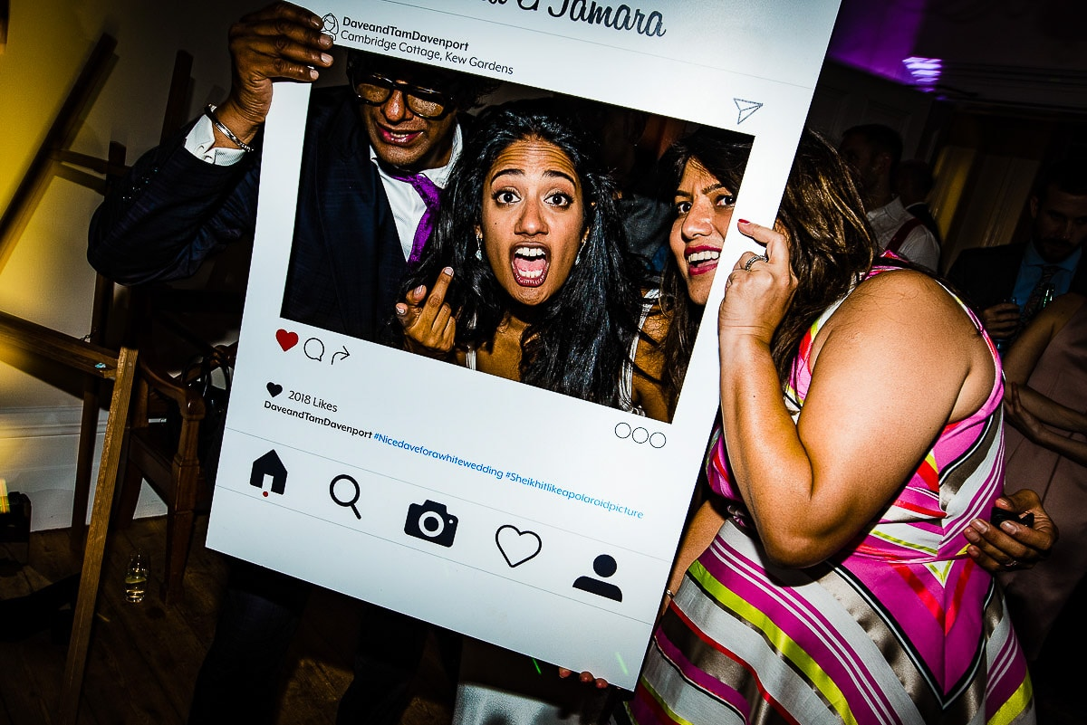 bride and guests pose through instagram photo mount
