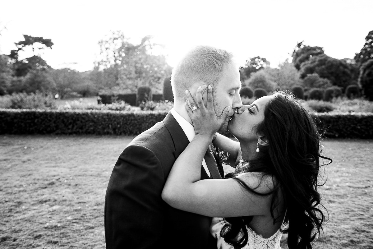 bride grabs groom's face and kiss as the sun sets in the garden