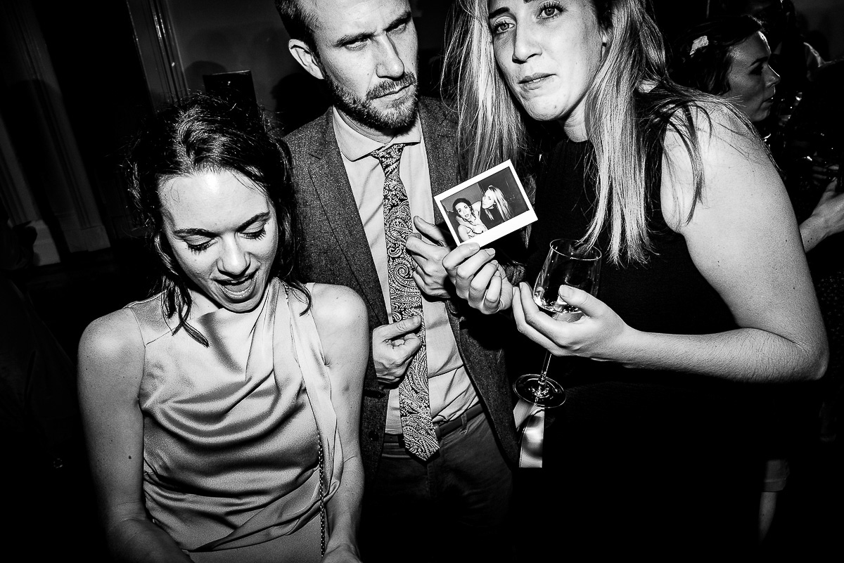 wedding guests pose with polaroid photo