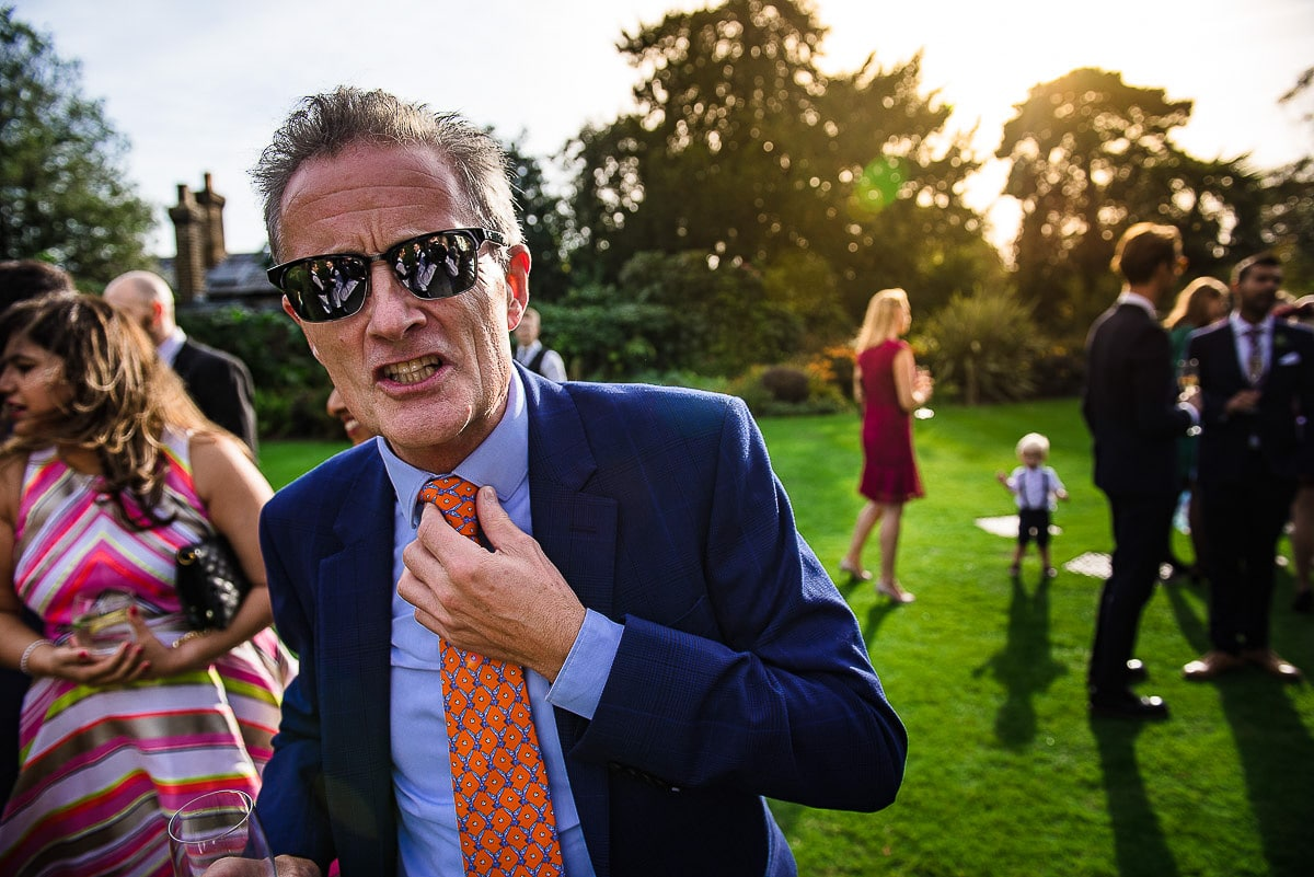wedding guest in sunglasses adjusts tie outside