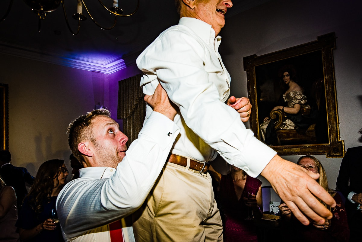Groom lifts up wedding guest on dancefloor