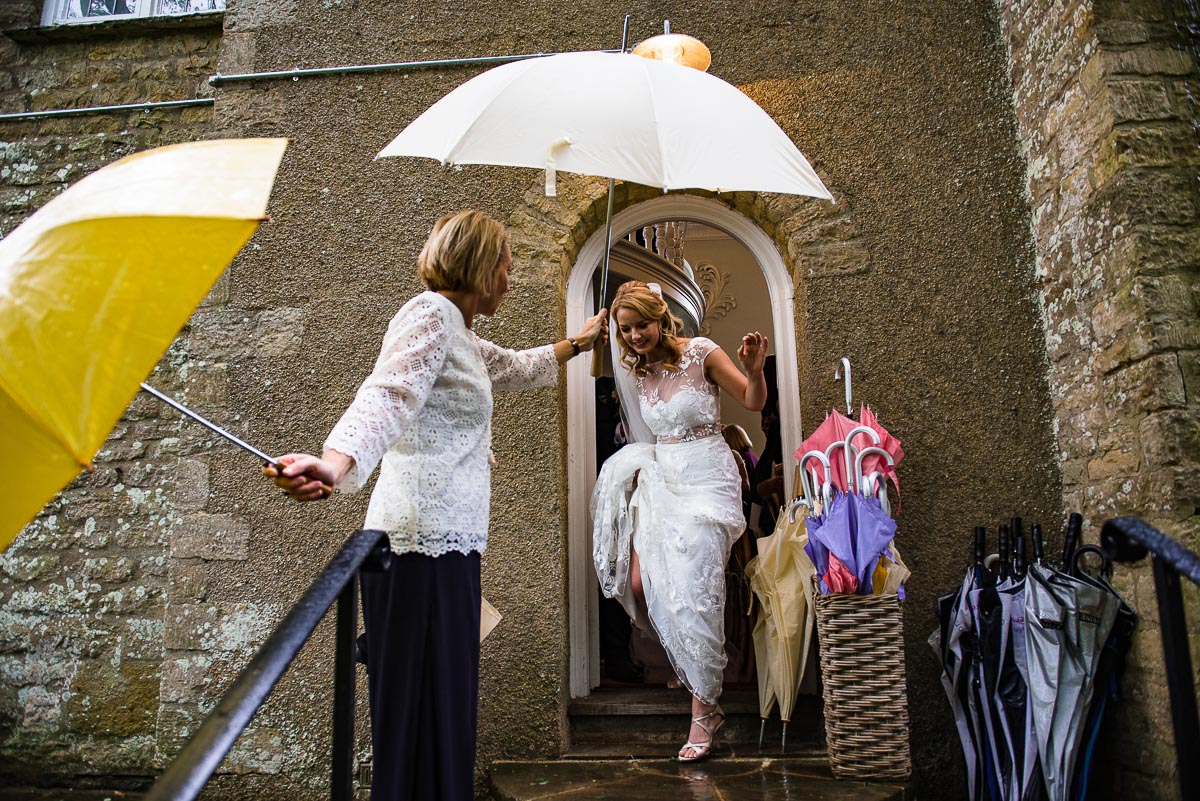 Cornwell manor guest holds up umbrella for bride as the rain pours down