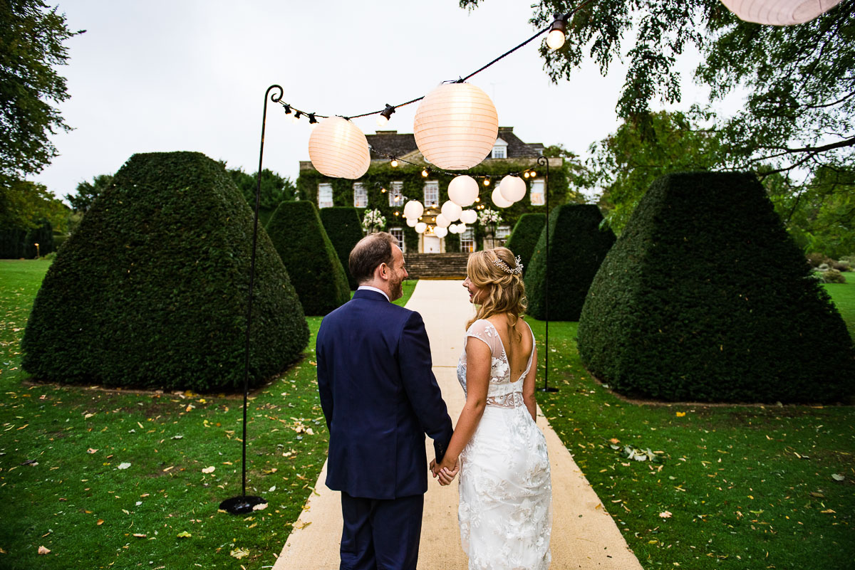 bride and groom admire Cornwell manor garden filled with lanterns
