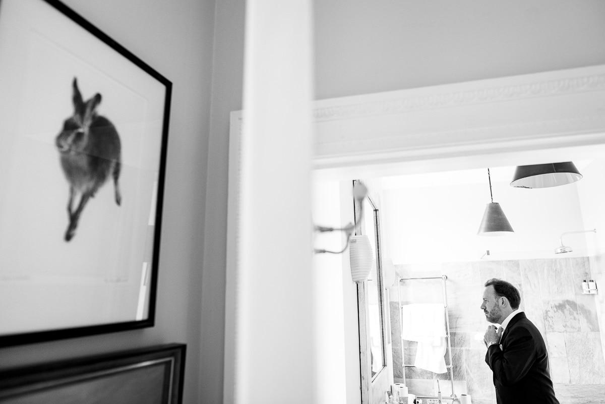 groom adjusts tie in Cornwell manor mirror detail
