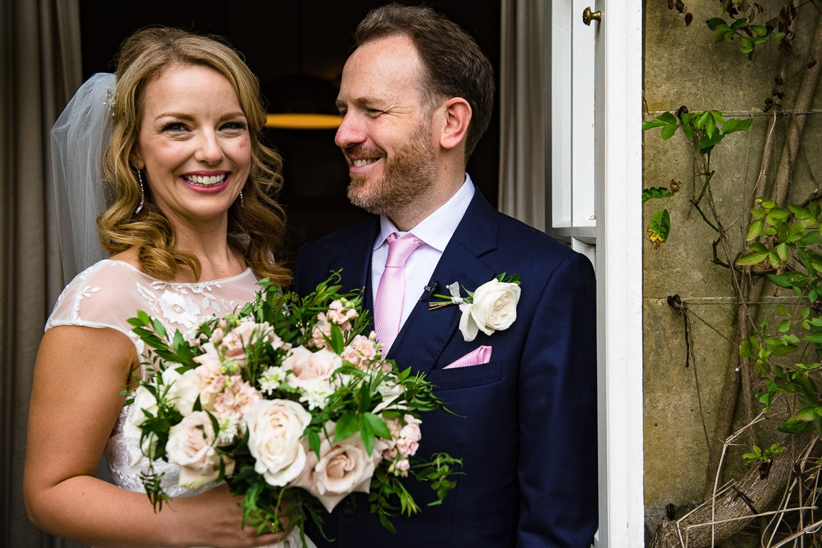 Smiling bride with bouquet and groom cornwell manor wedding