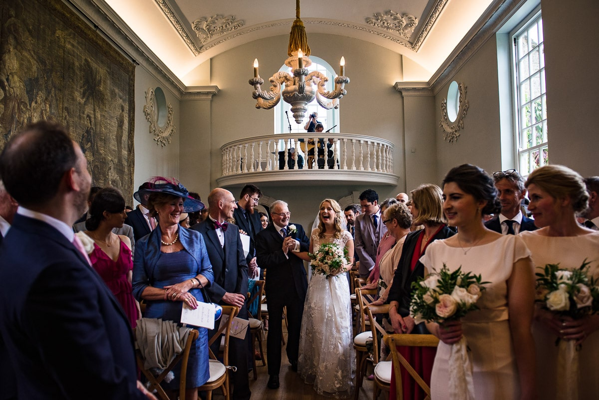 bride and father walk down the aisle at cornwell manor wedding venue