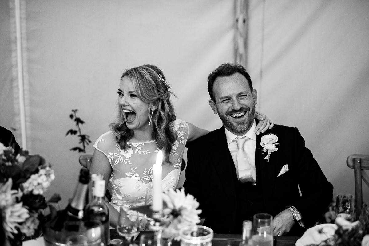 bride and groom laugh at wedding speeches in cotswold marquee