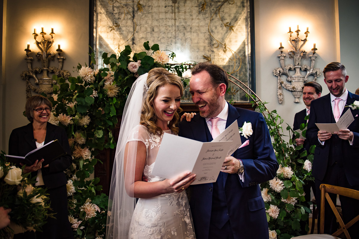 bride and groom laugh at hymns Cornwell manor wedding