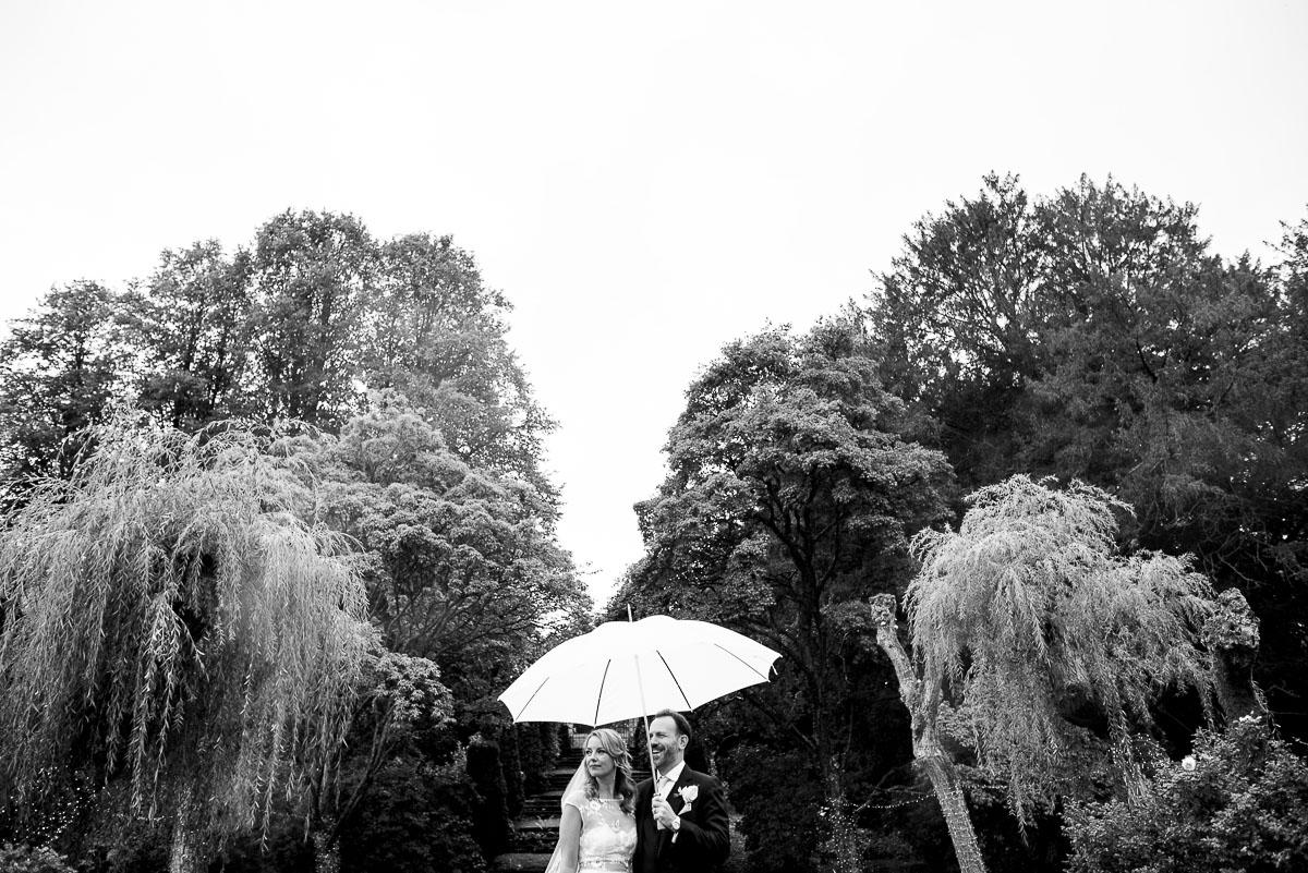 bride and groom hold umbrella aloft at Cotswold wedding venue