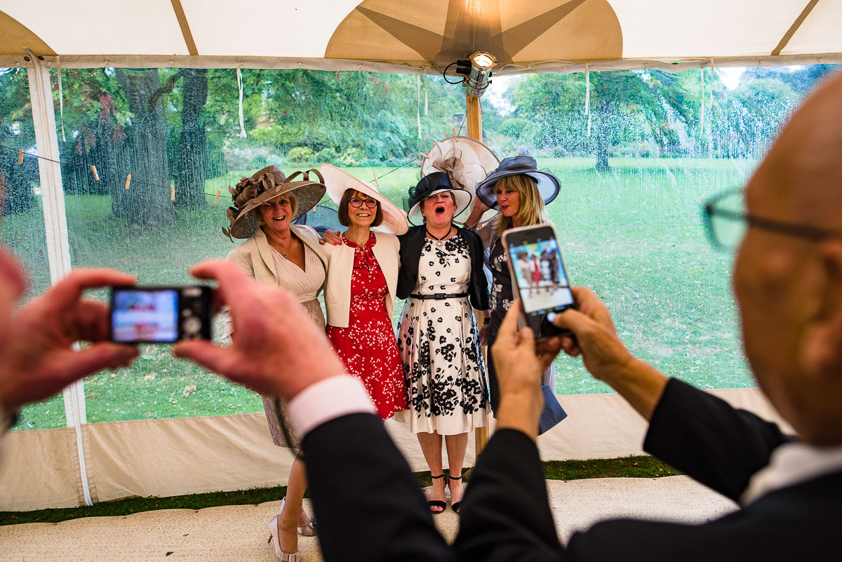 Four wedding guests in big hats pose for two cameras
