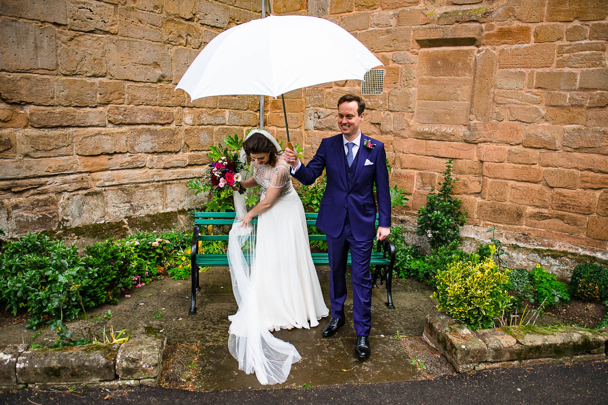 groom holds umbrella over bride as she adjusts her dress