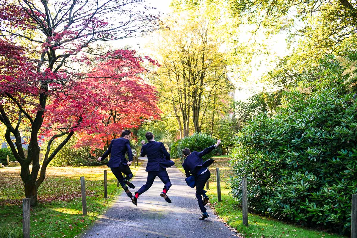 candid groom and groomsmen jump and skip along path