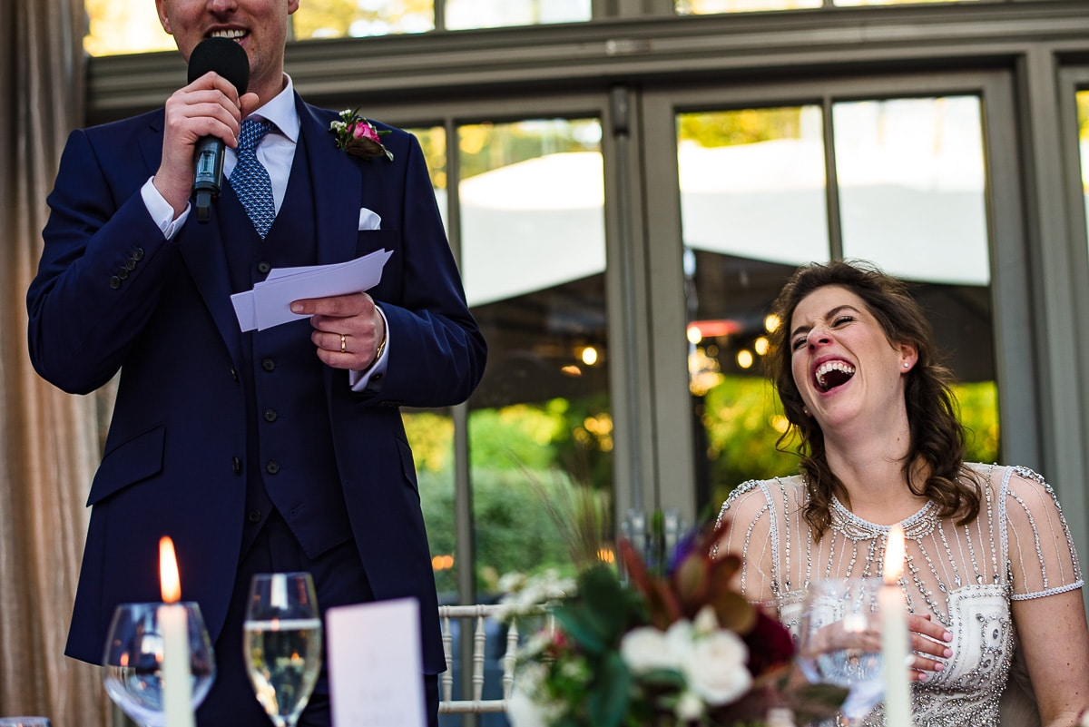 bride in hysterics as funny speech is made at dinner