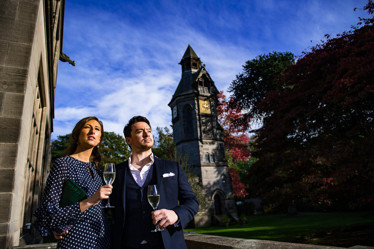 wedding guests admire the venue and drink champagne