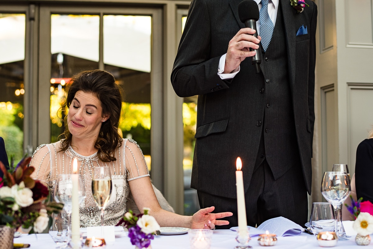 bride listens closely to wedding speech by groomsman
