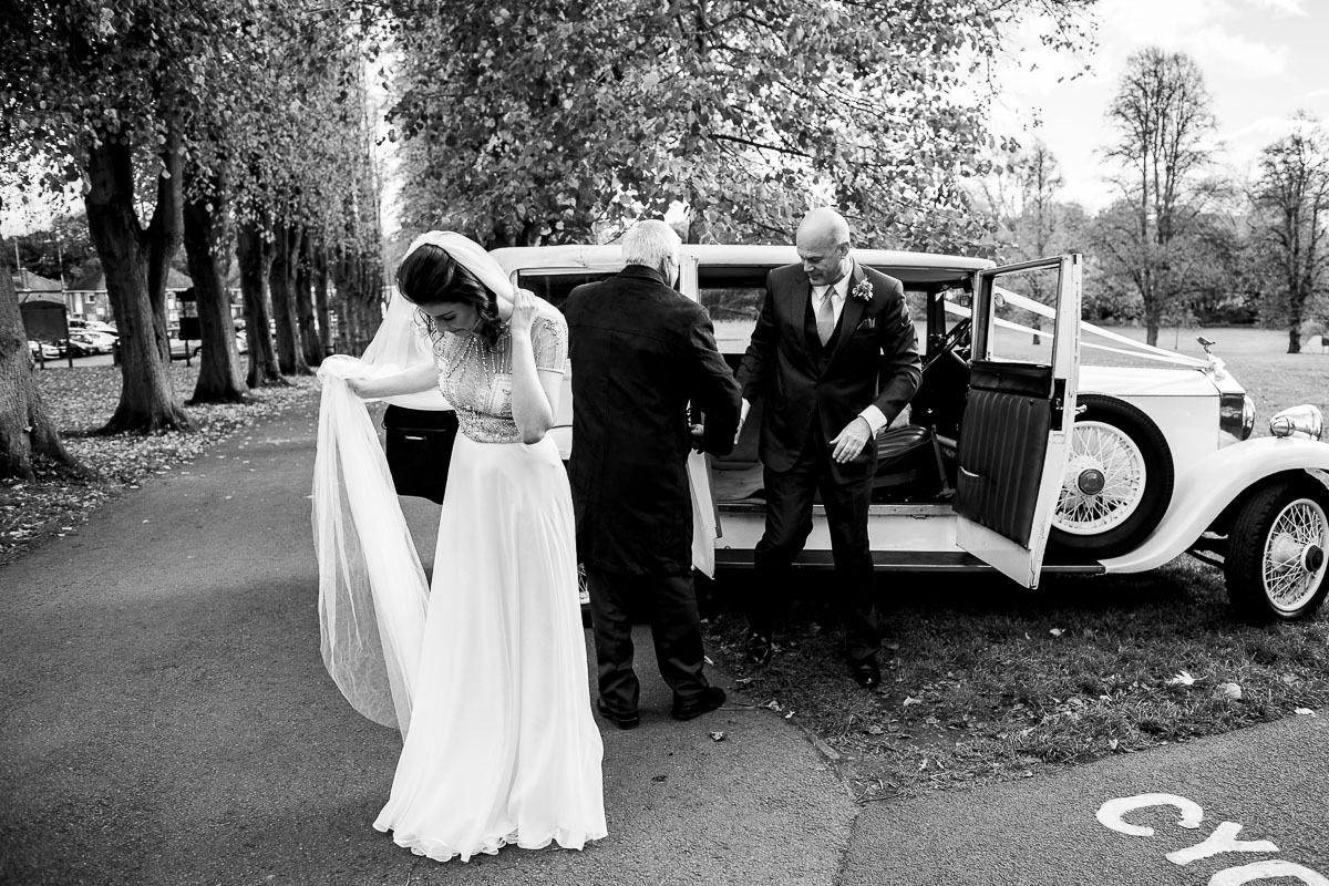 bride and her father arrive at the wedding venue in vintage car provided by wedding barn