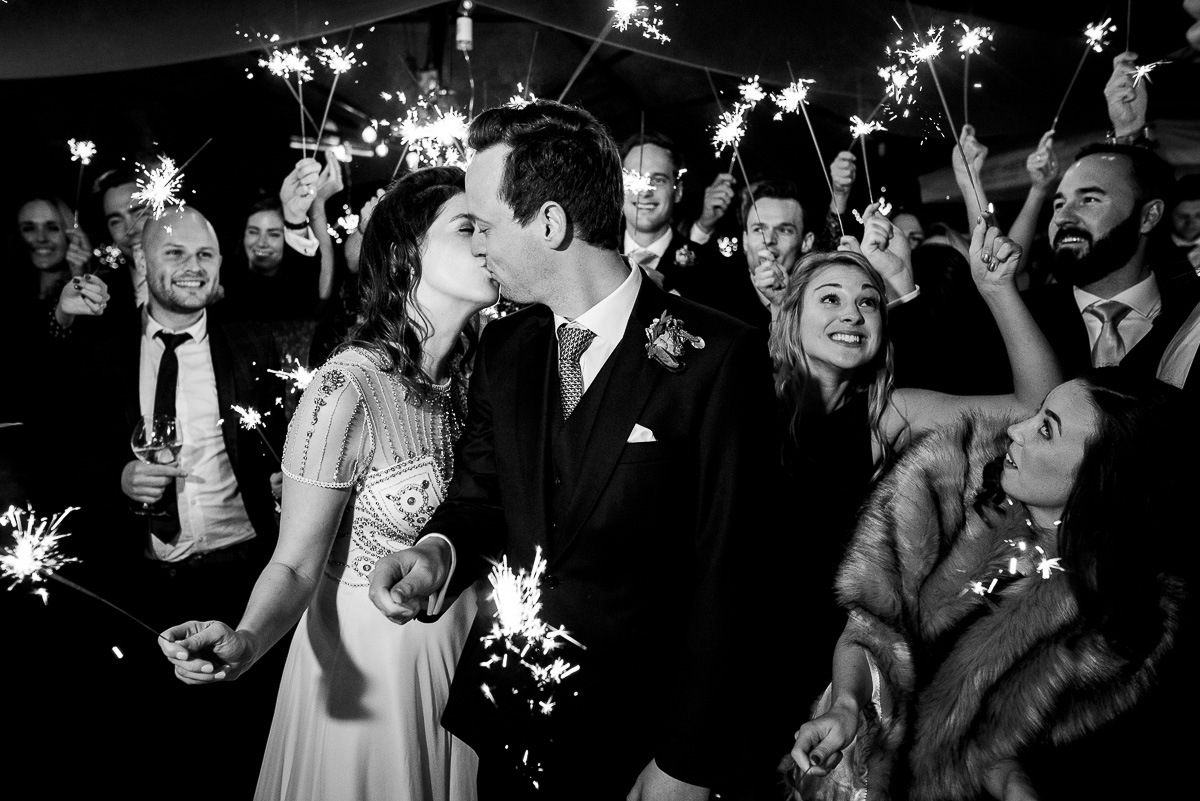 wedded couple kiss and guests celebrate with sparklers
