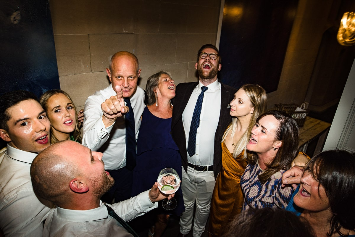 wedding guests gather to sing a song after having a drink