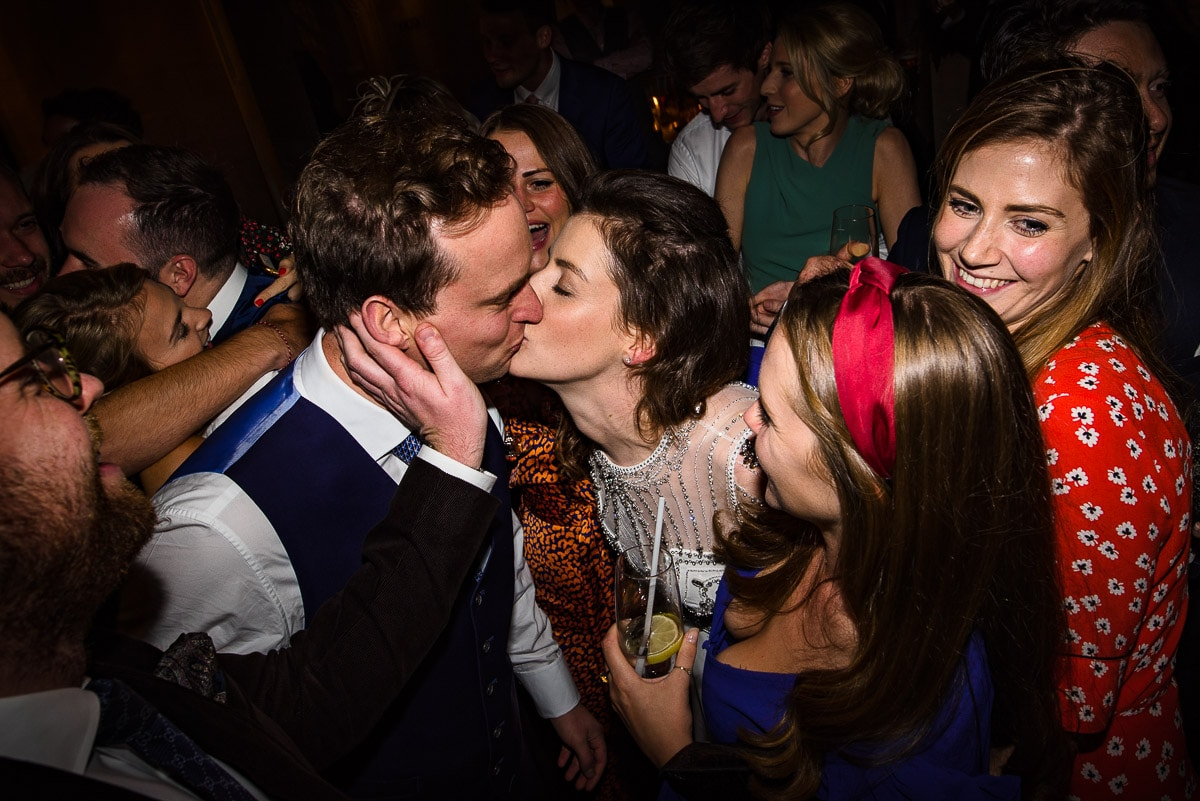guests cheer as bride and groom kiss on the dance floor