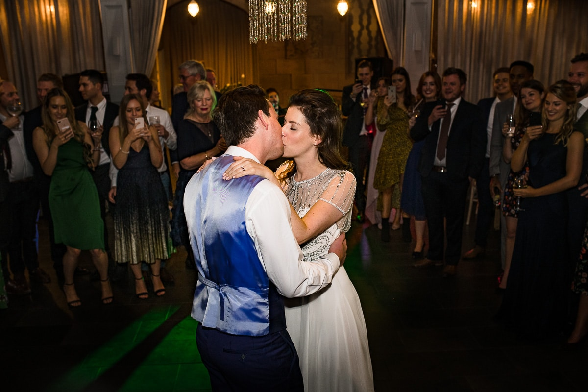 bride and groom kiss while having their first dance