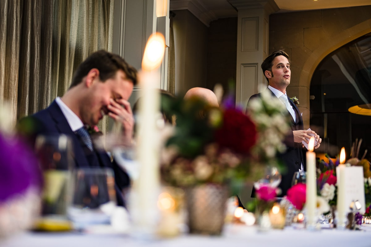 groom giggles at speech being read by his best man
