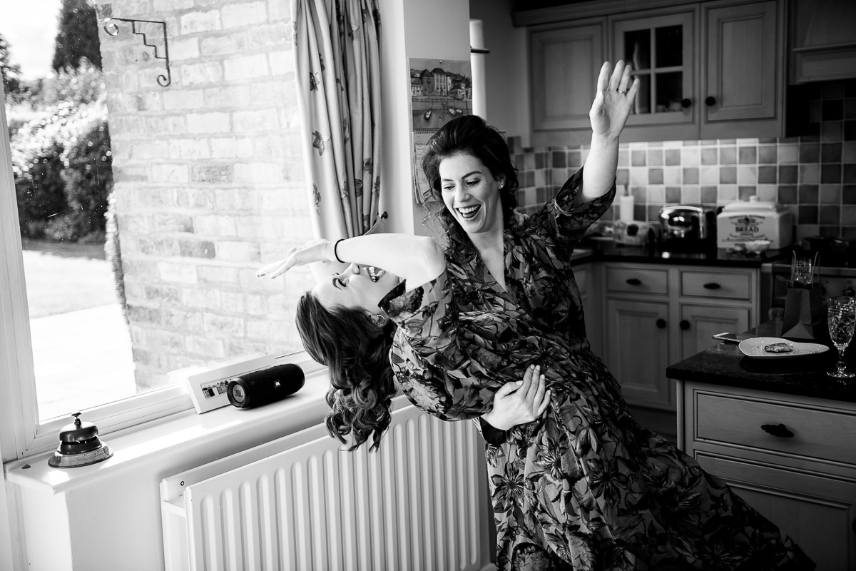 bride and bridesmaid dance in robes while prepping for the wedding