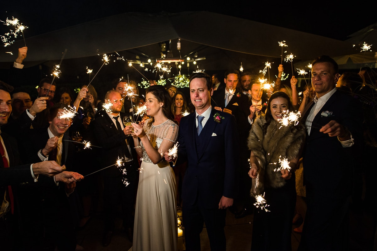 bride and groom look concerned at sparklers being lit
