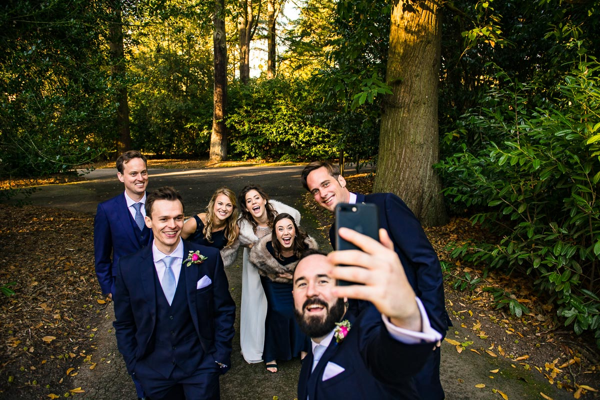 wedding guests take selfie in the woods