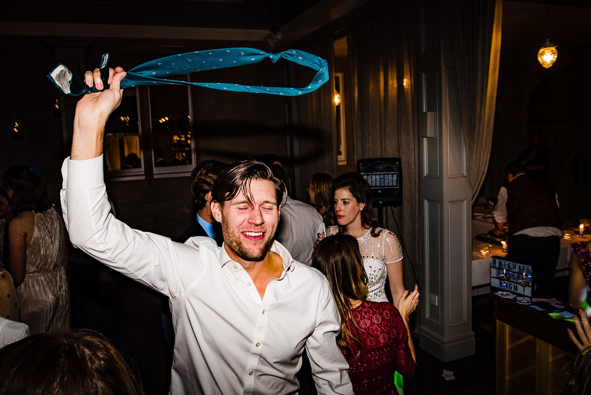 wedding guest takes off tie and starts partying on the dance floor