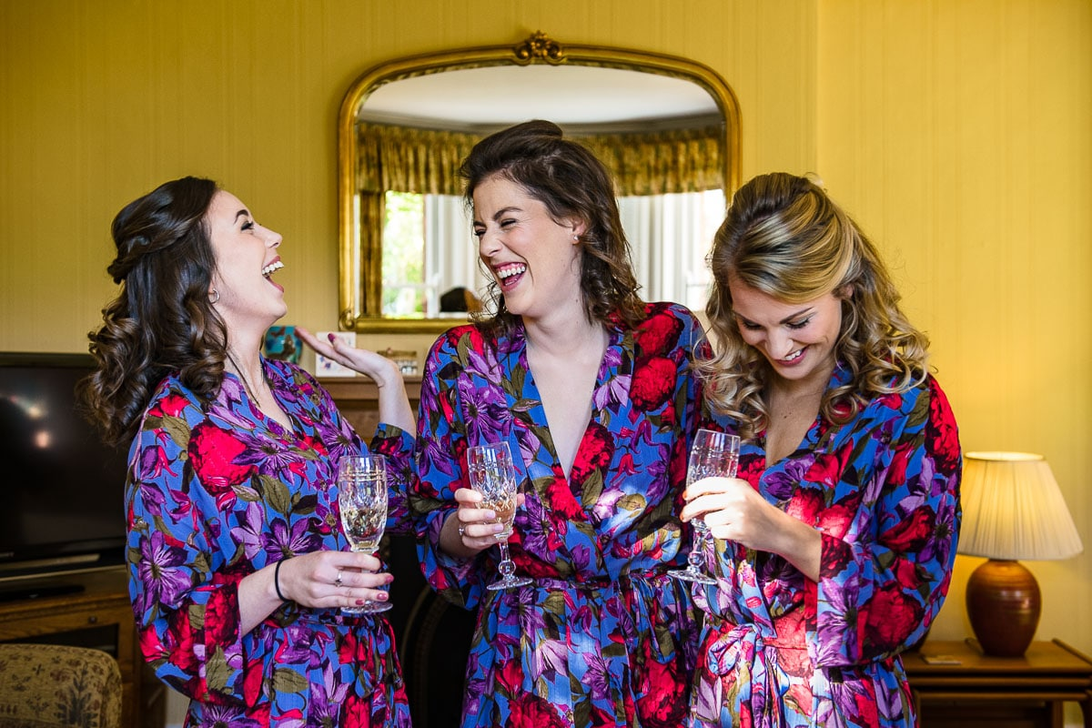 bride and bridesmaids laugh and have a glass of champagne before wedding