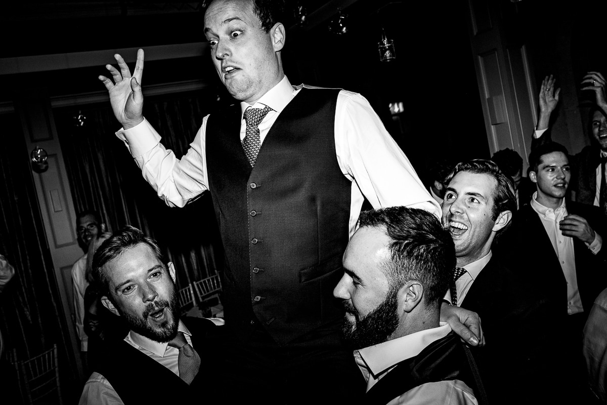wedding guest looks concerned as other guests lift him up