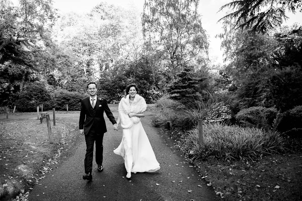 bride and groom stroll through the autumn garden
