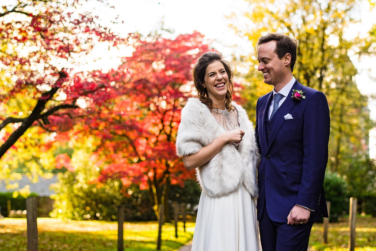 bride and groom in front of autumn trees at hampton manor