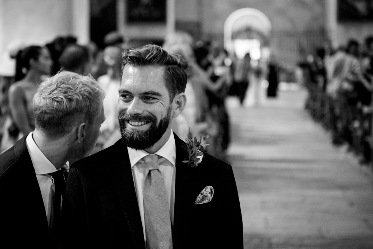 best man whispers to groom as bride walks down aisle