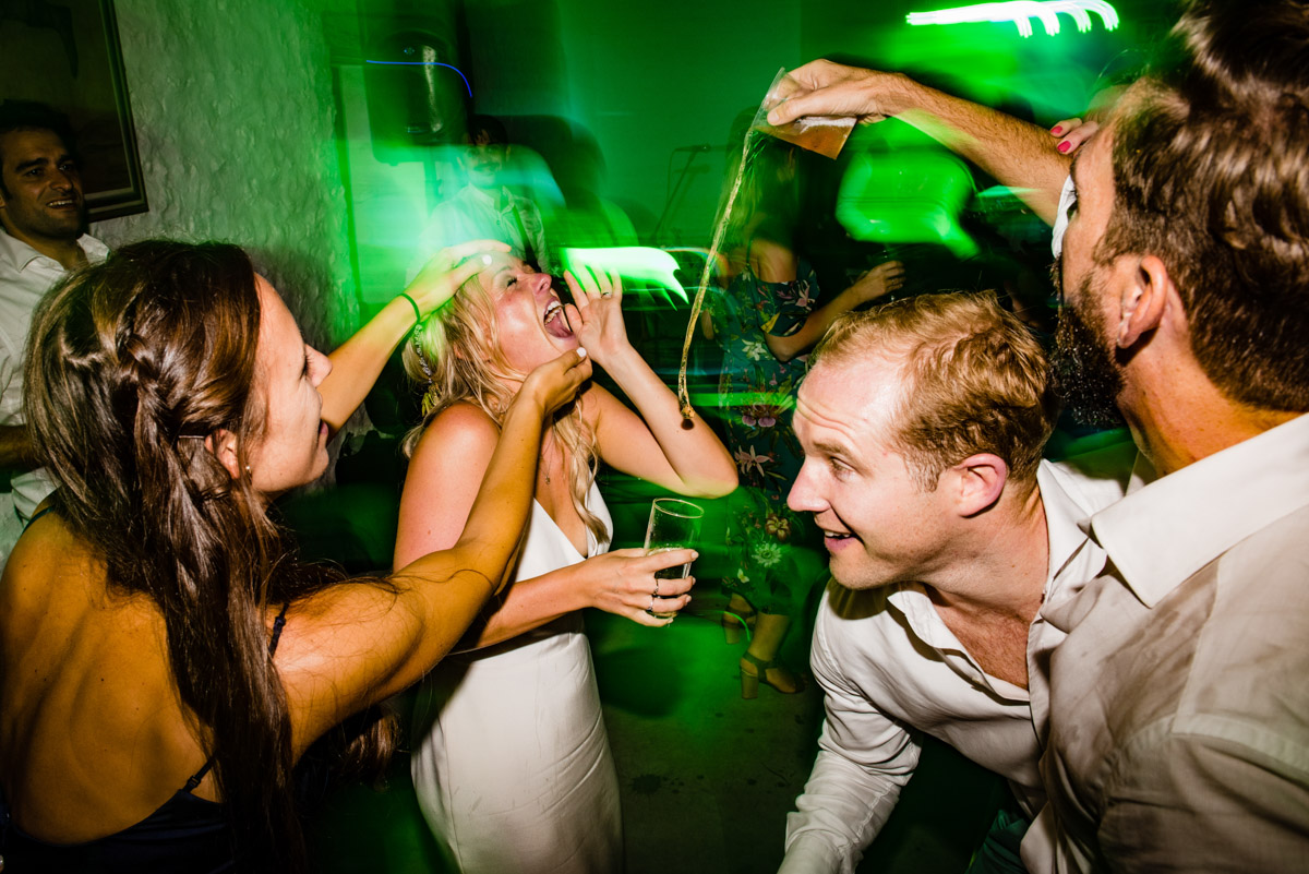 wedding guests pour drinks into each others mouths on dance floor