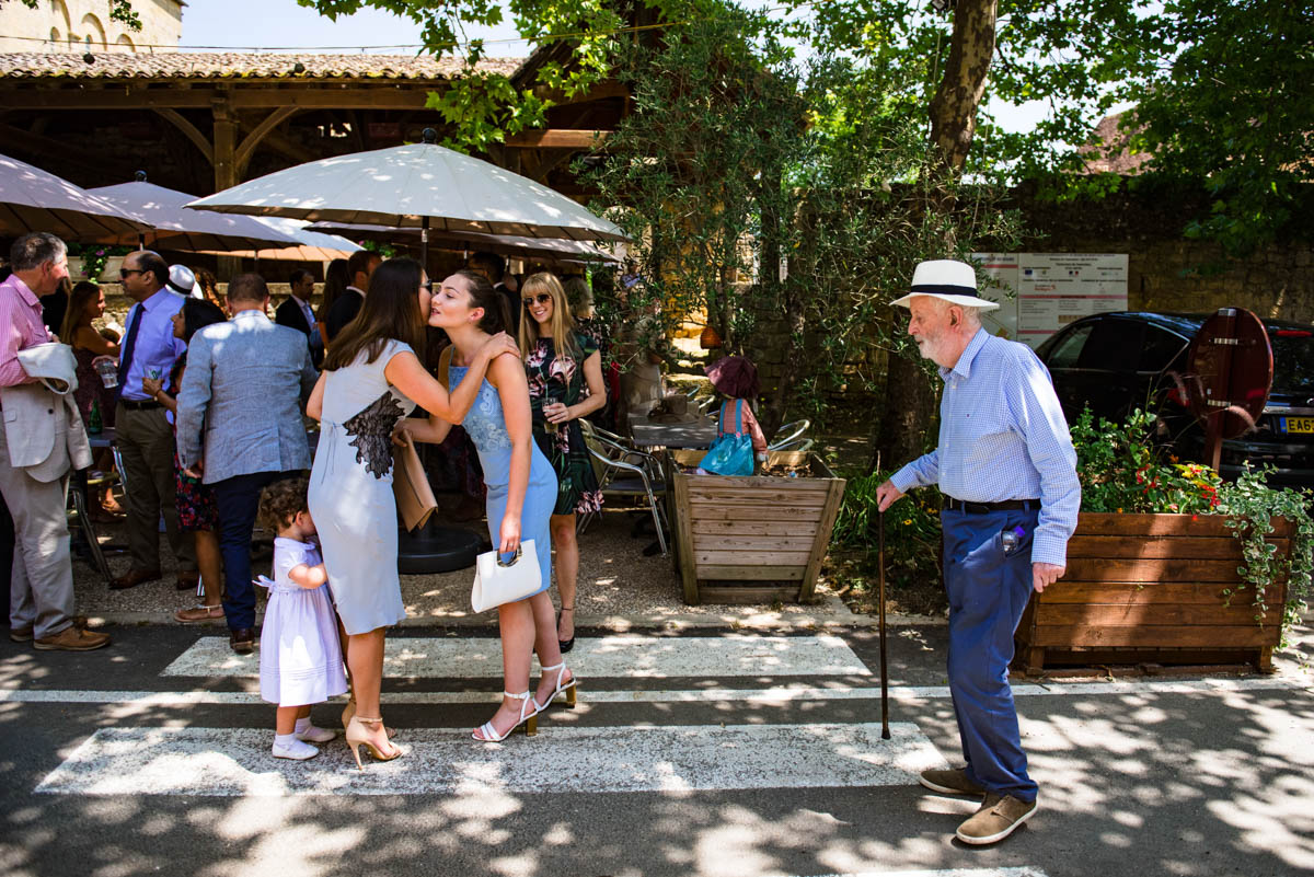 wedding guests greet each other in the shade