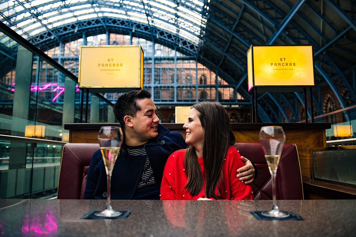 engaged couple celebrate with drinks at st pancras champagne bar