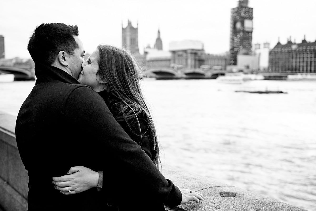 couple kiss on a bridge over the river Thames