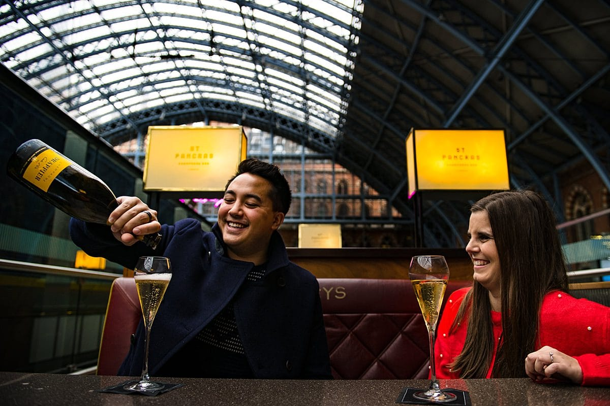 Couple pour champagne in booth at St Pancras station