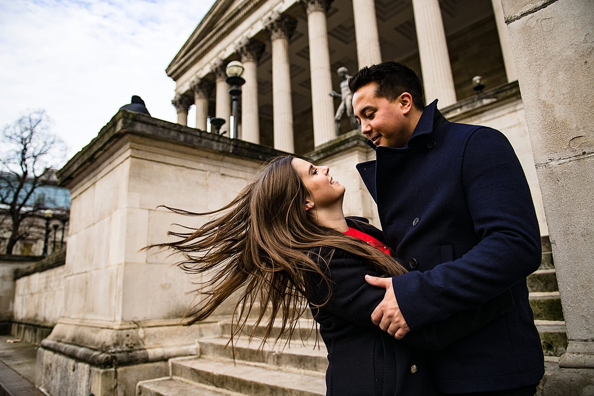 Windswept couple embrace outside old monument in London