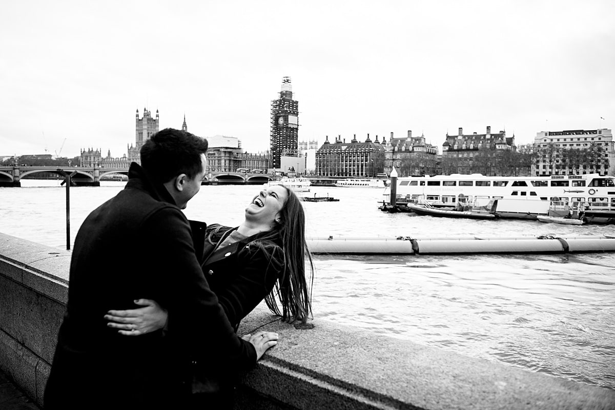 couple laugh on a bridge in London by river Thames