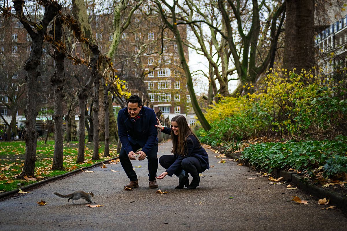 couple feed friendly squirrel in London park