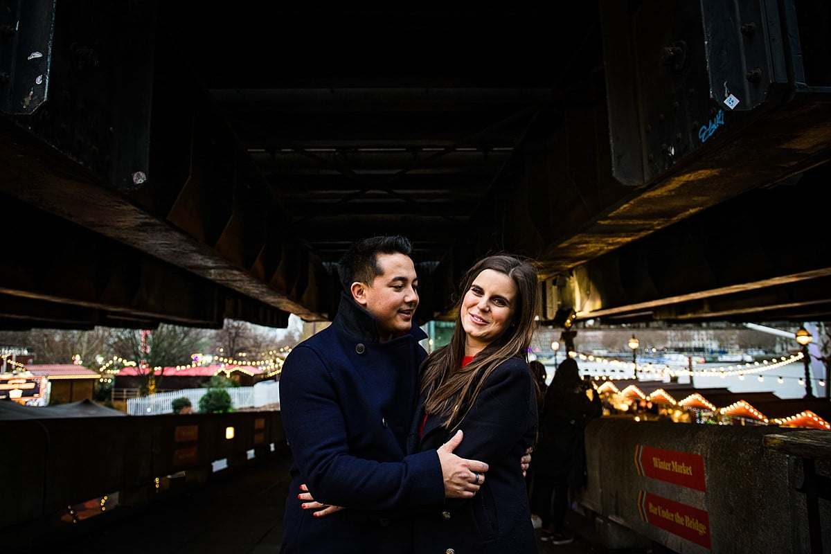 couple stand in front of Christmas market lights in London