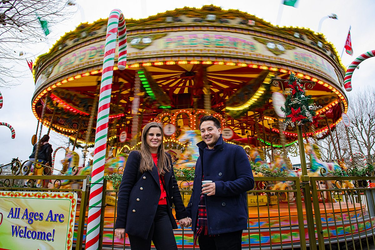 Engaged couple enjoy the Christmas carousel fun fair in London