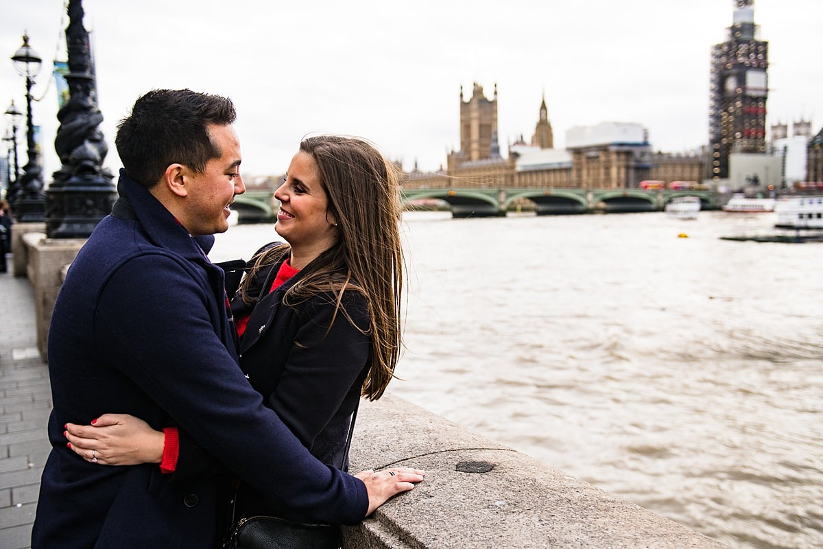 couple hug on street with London skyline by the river Thames