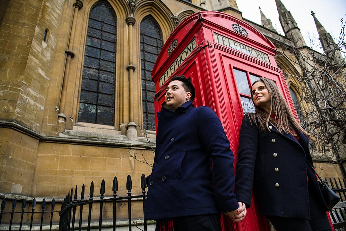 Engaged couple hold hands in front of iconic telephone box in London