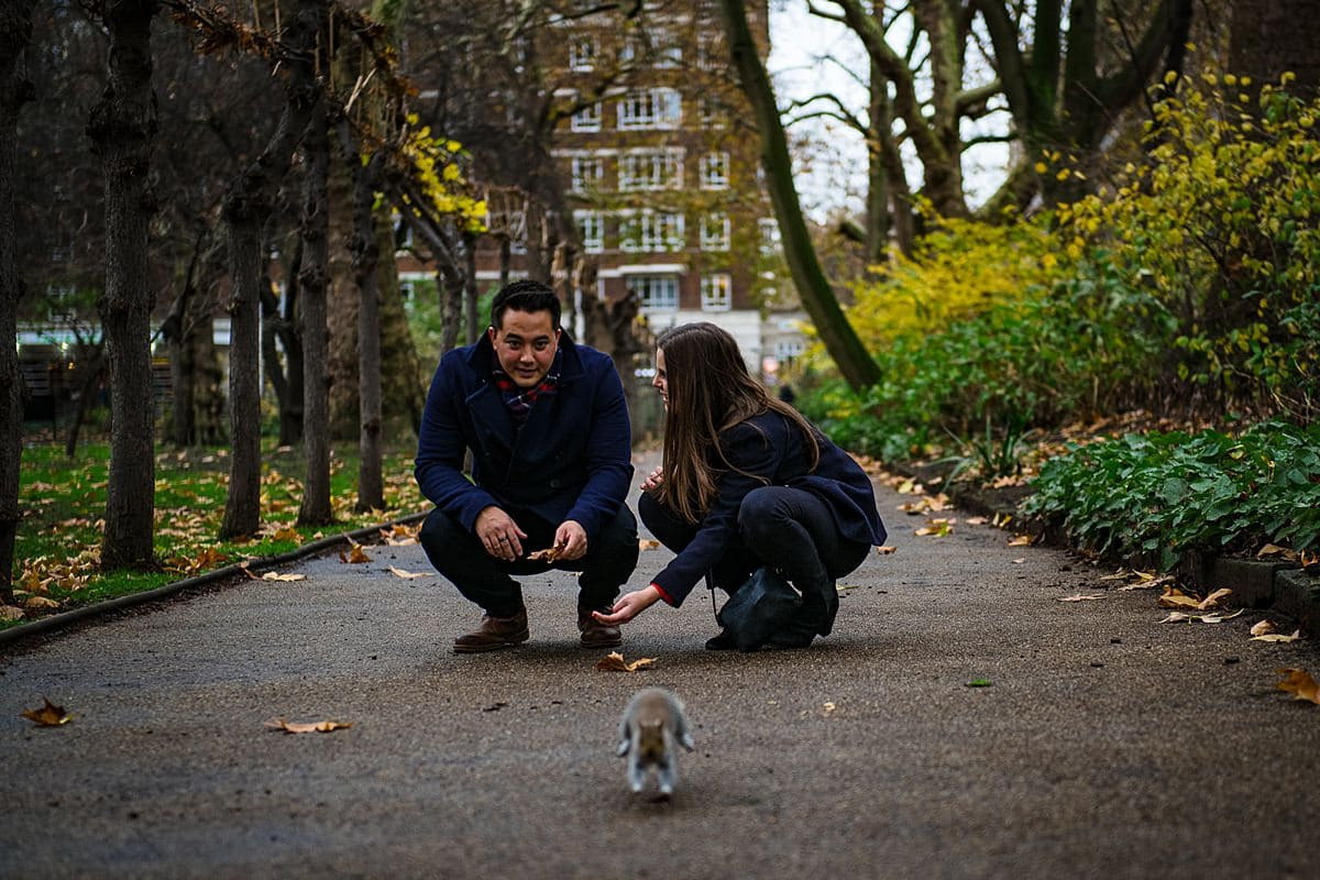 couple watch squirrel run away in London park