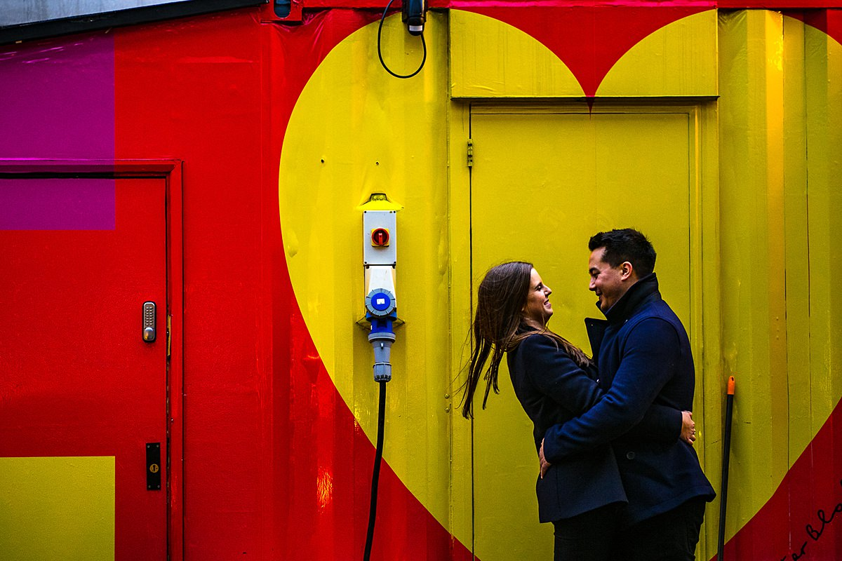 couple hug in front of London yellow heart street art
